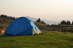 Tent on the mountains field. Tent in the sunset overlooking mountains and a valley Royalty Free Stock Photography
