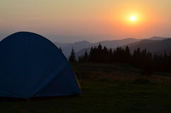 Tent on the mountains field. Tent in the sunset overlooking mountains and a valley Stock Images