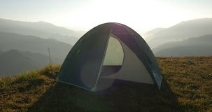Tent in the mountains. In transmitted light of the rising sun stock video footage