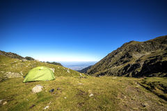 Tent in the mountains under the blue sky. In summer Stock Photography