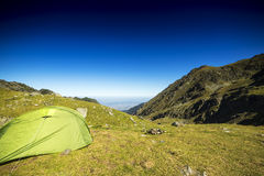 Tent in the mountains under the blue sky. In summer Stock Image