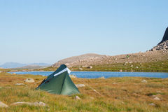Tent in the mountains. Wild camping in the mountains with a small lake in the background.  Summer solo camping.  Beautiful blue sky and sunshine Royalty Free Stock Image