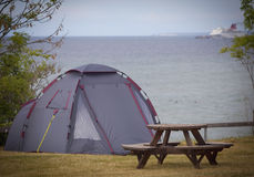 Tent next to the ocean.GN. Tent standing next to the ocean with a big ferry in the background at Gotland in Sweden.GN royalty free stock image