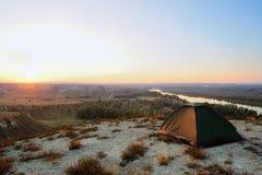Tent op de heuvel en rivier bij zonsondergang Royalty-vrije Stock Foto's