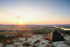 Tent op de heuvel en rivier bij zonsondergang Stock Fotografie