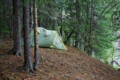 Tent op de steile bank van een wilde Siberische rivier wordt geïnstalleerd die royalty-vrije stock foto