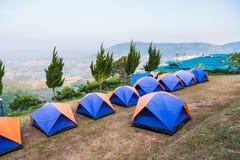 Tent op een gras onder witte wolken en blauwe hemel thailand stock afbeelding