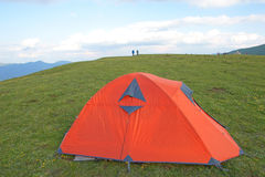Tent. The orange tent in green mountain meadow Royalty Free Stock Images
