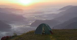 Tent over the clouds on the top of the hill stock video