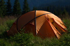 Tent  overlooking mountains and fir trees. Tent in the sunset overlooking mountains and a valley Stock Image