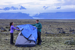 Tent - people pitching tent on Iceland at dusk Royalty Free Stock Photography