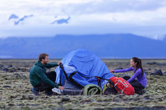Tent - people pitching tent on Iceland at dusk Royalty Free Stock Photos