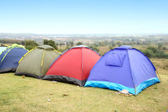 Tent pitched on lush green mountain hillside Stock Images