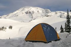 Tent and Rainier. A single tent is pitched high up on Mt. Rainier with the peak located directly behind it. This photograph was taken just after sunrise royalty free stock photos