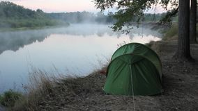 Tent on the river bank. Fog rises above the river. dawn stock video