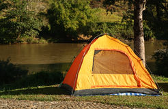Tent beside river Stock Photo