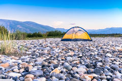 Tent on riverbed rock beach Royalty Free Stock Images