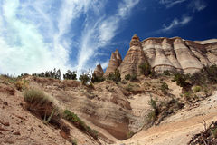 Tent Rocks. View of hoodoos and surrounding desert landscape against clouded blue sky from canyon floor at Tent Rocks monument in New Mexico royalty free stock image