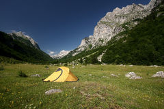 Tent on Ropojana Valley. An yellow tent on a green meadow at the foot of a mountain. Ropojana Valley, Prokletije Mountains, or Albanian Alps, Montenegro Stock Image