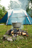 Tent and saucepan on a fire. Kettle on a burning fire, and tourist tent Stock Photo