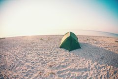 Tent on the beach. Tent on the sea coast. Camping on the ocean coast. Rest on the sandy beach Royalty Free Stock Images