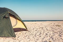 Tent on the beach. Tent on the sea coast. Camping on the ocean coast. Rest on the sandy beach Royalty Free Stock Photography
