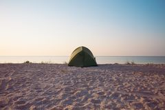 Tent on the beach. Tent on the sea coast. Camping on a sandy beach. Rest in a deserted place Royalty Free Stock Photography
