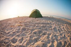Tent on the beach. Tent on the sea coast. Camping on a sandy beach. Rest in a deserted place Stock Images
