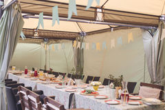 Tent with served table inside. Long served table for event served under tent with decorations Stock Photos