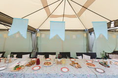 Tent with served table inside. Long served table for event served under tent with decorations Royalty Free Stock Image