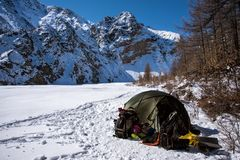A tent is set up in a high mountain environment. With backpack Royalty Free Stock Image
