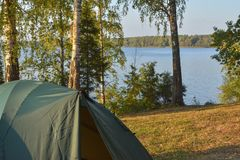 Tent on the shore of the reservoir, autumn shore of the lake, tent in the autumn forest royalty free stock photo