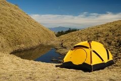 Tent and small lake. In high mountain stock photo