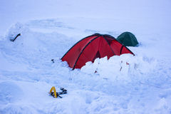 Tent in the snow in the mountains. Cold winter hike overnight in a tent in the snow in the mountains Royalty Free Stock Images