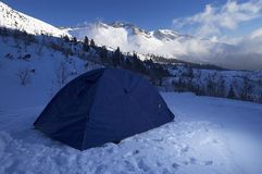 Tent in Snowy Mountains. Blue tent pitched in snow covered mountains Royalty Free Stock Images