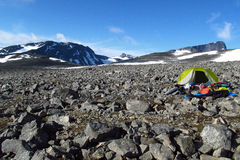 A tent stanging in rocky mountain peaks and glacier in Norway Royalty Free Stock Photos