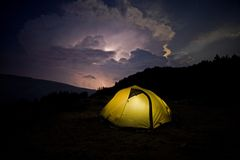 Tent before the storm. An illuminated tent at night and a far away storm Royalty Free Stock Photo