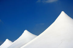 Tent Tops. White tent tops against blue sky royalty free stock photos