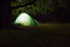 A tent under an old oak in the night Stock Photo