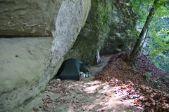 Tent under a rock in the forest Royalty Free Stock Image