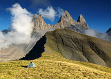 Tent under three peaks Aiguilles d'Arves in French Alps, France. Aiguilles d'Arves, Grandes Rousses, Dauphine Alps, France Royalty Free Stock Images
