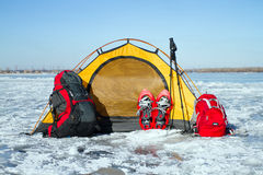 Tent winter mountains.Tent stands in the mountains in the snow. Snowshoes are beside the tent. Royalty Free Stock Images
