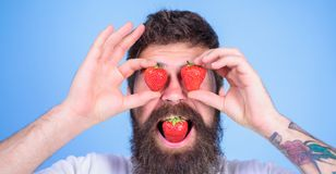 Tentation douce Homme dans l'amour avec la fraise Le hippie avec la barbe mange des baies de fraise et de prise comme lunettes Ho Image libre de droits