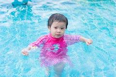 Tentativa asiática pequena da menina que nada apenas na piscina, exterior foto de stock