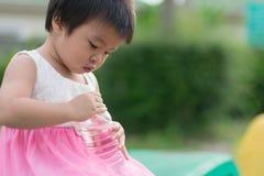 Tentativa bonito pequena asiática da menina para fechar a garrafa plástica de limpo fotografia de stock royalty free