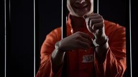 Tentativa criminosa destravar as algemas, estando atrás das barras, escape da prisão imagem de stock royalty free