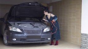 Tentativa da jovem mulher para conectar cabos de ligação em ponte com o motor de automóveis filme