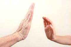 Tentativa da mão do ` s da criança para tocar na mão superior ou na mão da mulher adulta seleto Fotografia de Stock