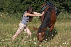 Tentativa da menina para mover um sorrel Fotografia de Stock Royalty Free