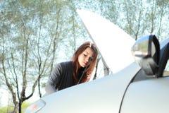Tentativa da mulher para encontrar um problema no motor de automóveis Fotografia de Stock Royalty Free